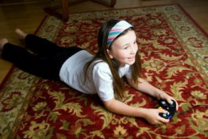 Girl lying on clean area rug playing video games